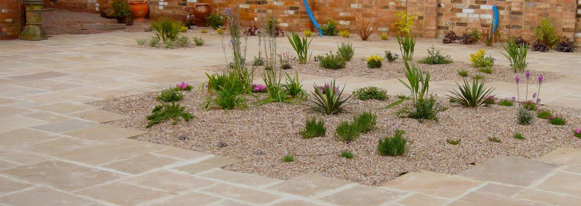 Paved patio with small plant islands in the middle of paving.