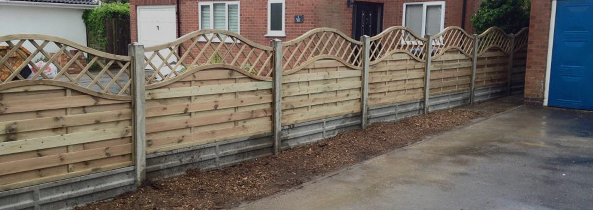 Wooden fence fitted by Outback landscapes in between two brick houses.