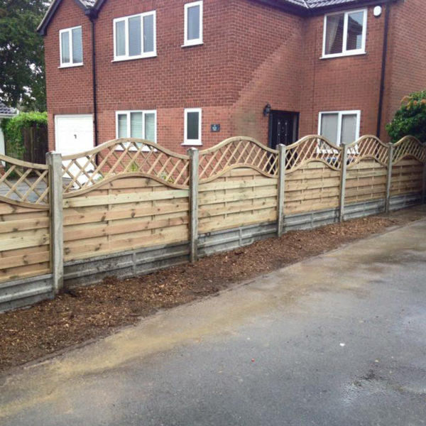 Newly installed wooden fence between two houses made from brick.
