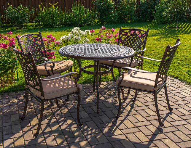 Patio made from bricks with round table and four garden chairs placed in the private garden.